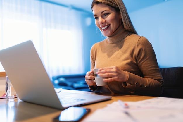Jeune femme entrepreneur blonde souriante attrayante assis à la maison, boire du café et regarder un ordinateur portable