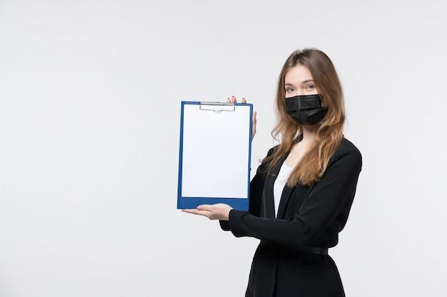 Jeune femme entrepreneur confiante en costume portant son masque médical et montrant des documents sur un mur blanc