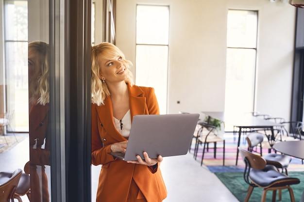 Jeune femme entrepreneur à la mode joyeuse avec un ordinateur portable à la main, debout au bureau