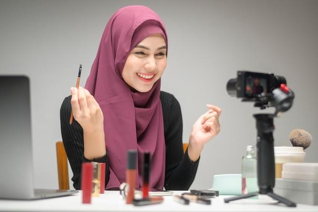 Une jeune femme entrepreneur musulmane travaillant avec un ordinateur portable présente des produits cosmétiques au cours de la diffusion en direct en ligne sur fond blanc studio, vente en ligne et concept de blogueur de beauté