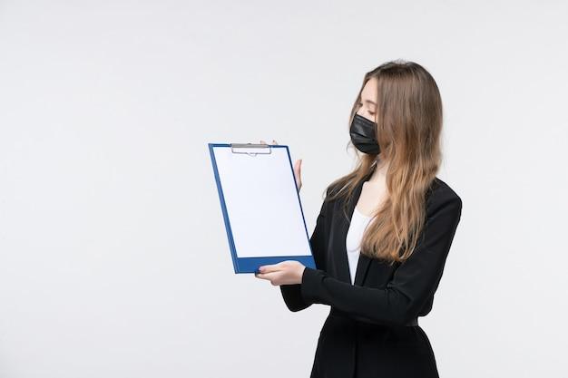Jeune femme entrepreneur rêveuse en costume portant son masque médical et montrant des documents sur un mur blanc