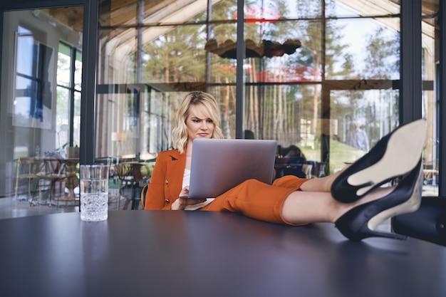 Jeune femme entrepreneur sérieuse dans un tailleur-pantalon assis avec ses jambes posées sur le bureau