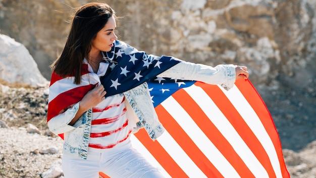 Jeune femme enveloppée dans le drapeau à la recherche de suite