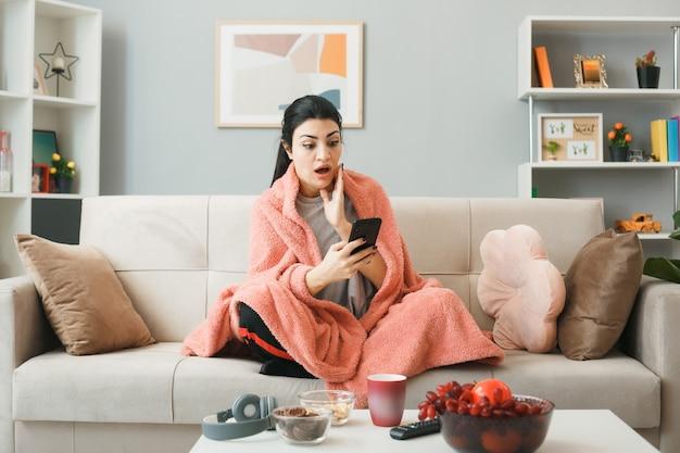 Jeune femme enveloppée dans un plaid tenant et regardant le téléphone assis sur un canapé derrière une table basse dans le salon