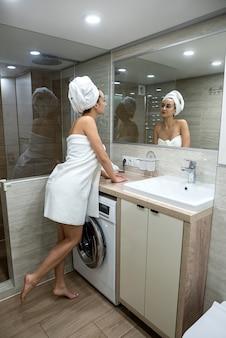 Jeune femme enveloppée de serviettes après avoir pris une douche, tôt le matin