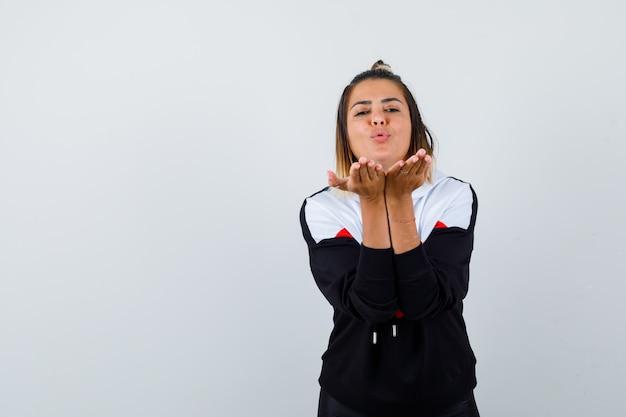 Jeune femme envoyant un baiser aérien dans un pull à capuche et très jolie.