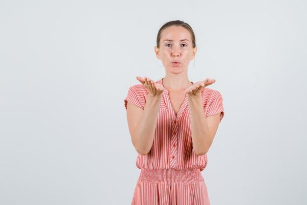 Jeune femme envoyant un baiser d'air en robe rayée, vue de face.