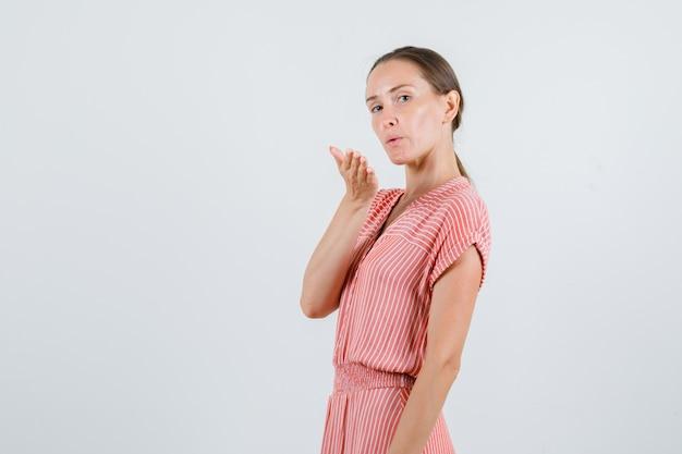 Jeune femme envoyant un baiser d'air en robe rayée.