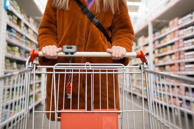 Jeune, femme, épicerie, charrette, étagères, épicerie, magasin