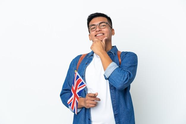Jeune femme équatorienne tenant un drapeau du royaume-uni isolé sur fond blanc heureux et souriant