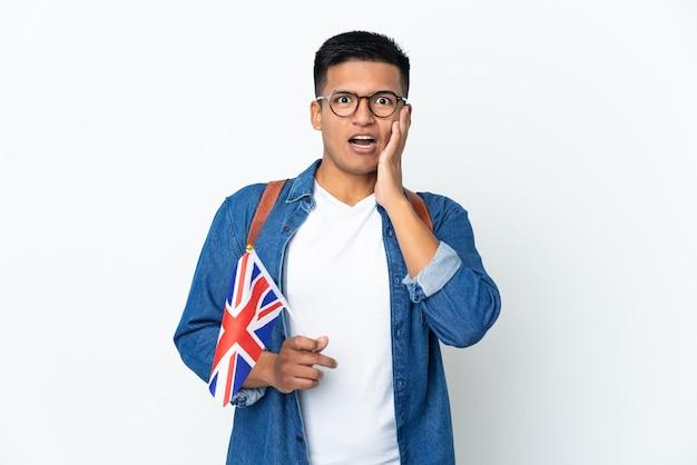 Jeune femme équatorienne tenant un drapeau du royaume-uni isolé sur un mur blanc avec surprise et expression du visage choqué