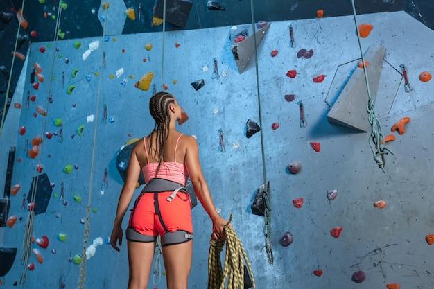 Jeune femme en équipement d'escalade avec une corde