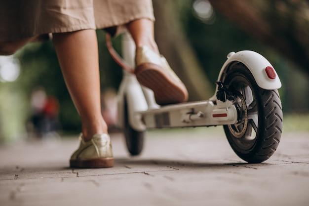 Jeune femme, équitation, scooter, dans, parc, pieds, gros plan
