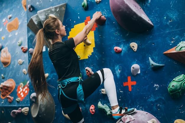 Jeune femme escaladant un grand mur d'escalade artificiel, à l'intérieur