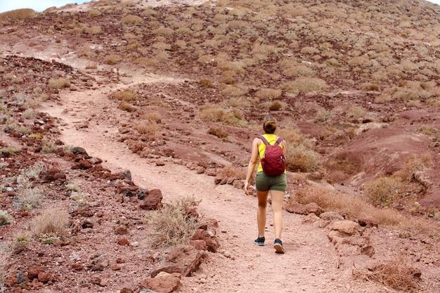 Jeune Femme Escalade Une Montagne Avec Fond Rouge Photo Premium