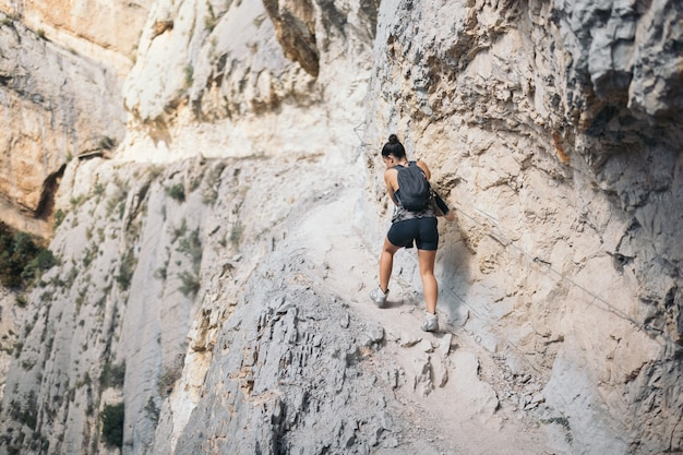 Jeune femme escalade randonnée sur une montagne étroite