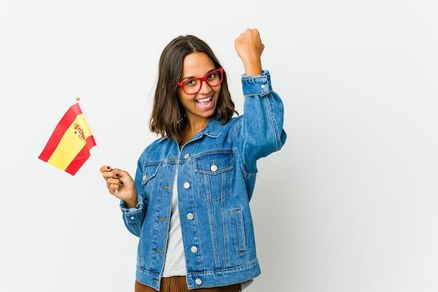 Jeune femme espagnole tenant un drapeau isolé sur un mur blanc applaudissant insouciant et excité. concept de victoire.