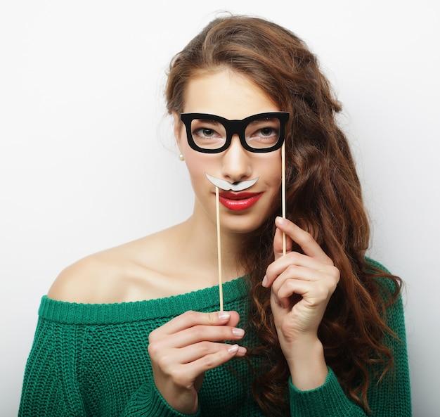 Jeune femme espiègle tenant des lunettes de fête et une fausse moustache