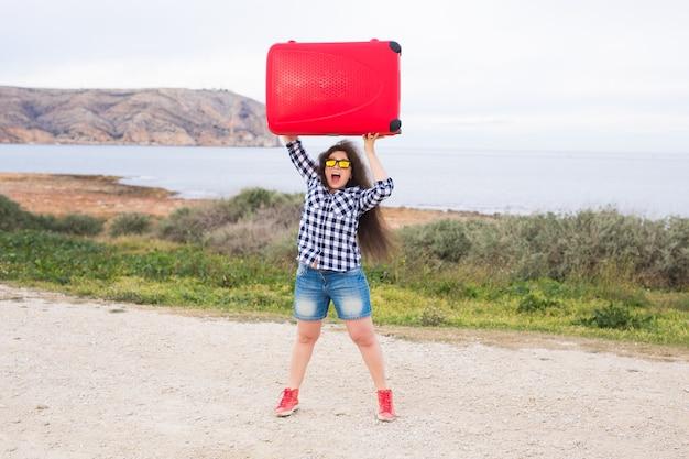 Jeune femme essaie de soulever ses bagages