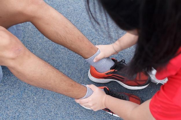 Une jeune femme essaie de verrouiller la cheville de son amie pour la situer. concept d'entraînement