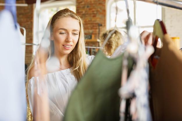 Jeune femme essayant un chiffon, à la recherche d'une nouvelle tenue