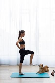Jeune femme essayant de faire du sport à la maison avec son chien