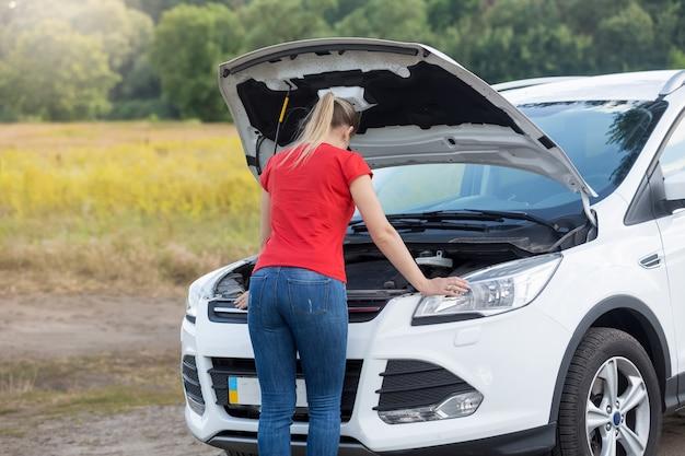 Jeune femme essayant de réparer la voiture en panne à la route rurale