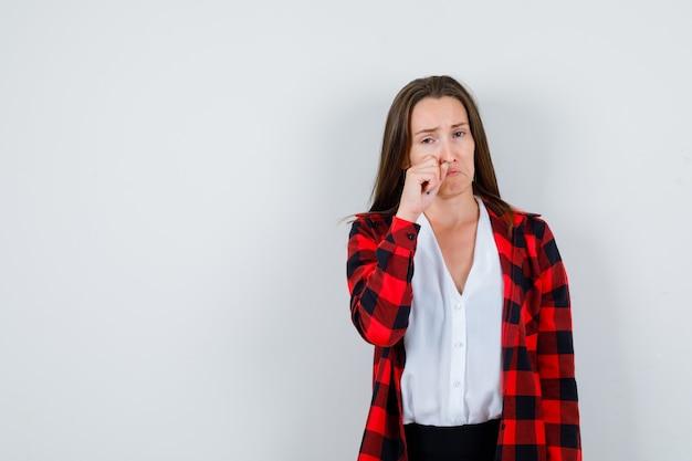 Jeune femme essuyant les larmes avec la main dans des vêtements décontractés et l'air déprimé, vue de face.