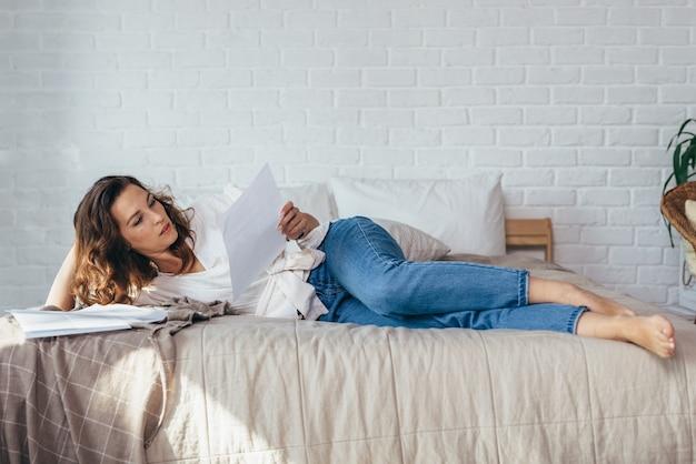 Jeune femme est allongée sur son lit à la maison en train de lire des documents.