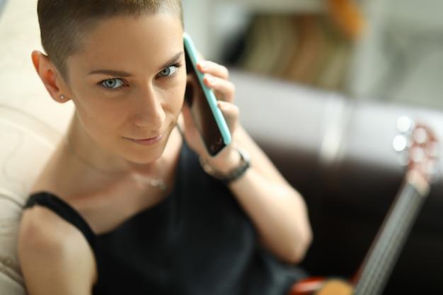 Jeune femme est assise sur un canapé avec une guitare et parle au téléphone