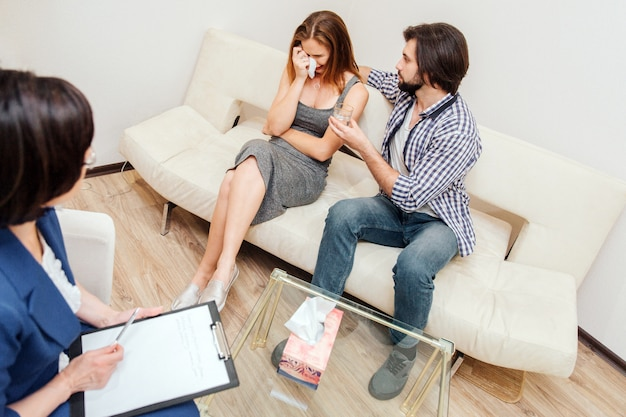 Jeune femme est assise sur le canapé et pleure. elle enveloppe ses yeux avec une serviette sèche. son mari est enlacé ici. il veut qu'elle se sente en sécurité et confortable. le psychologue les regarde.