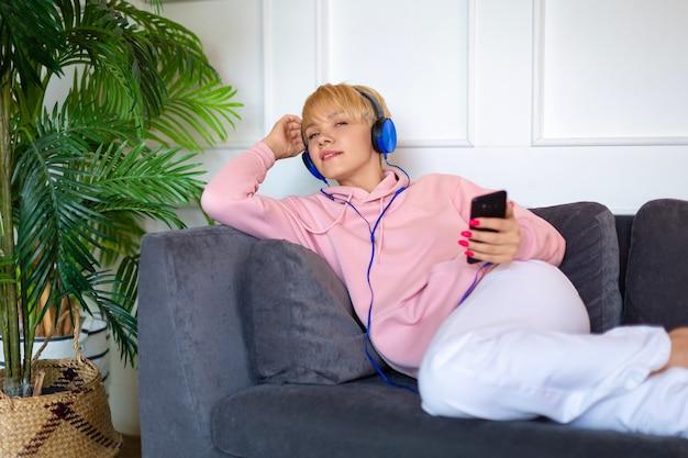 Une jeune femme est assise sur le canapé avec une tablette et écoute de la musique avec des écouteurs