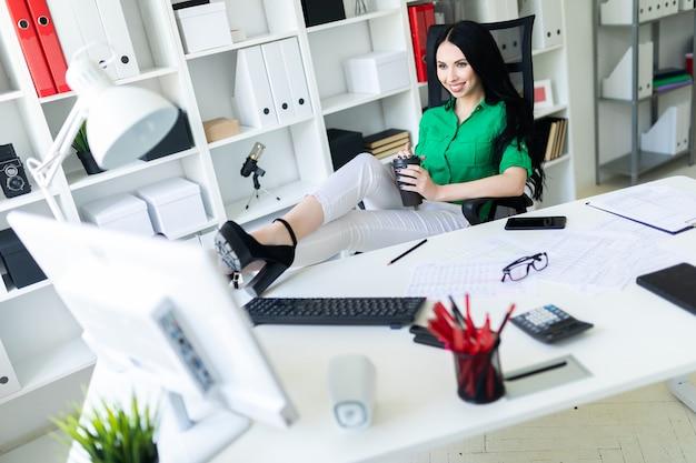 Une jeune femme est assise dans le bureau, a jeté ses jambes sur la table et tient un verre de café.