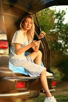 Une jeune femme est assise dans le coffre ouvert d'une voiture et mange une pomme verte.