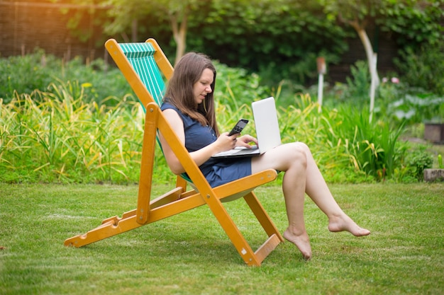 Une jeune femme est assise dans un pré avec un ordinateur portable et parle lors d'une conférence en ligne au travail