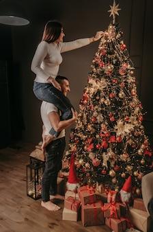 Jeune femme est assise sur les épaules arrière de l'homme et décore un arbre de noël