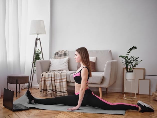 Jeune femme est assise sur une ficelle à la maison.