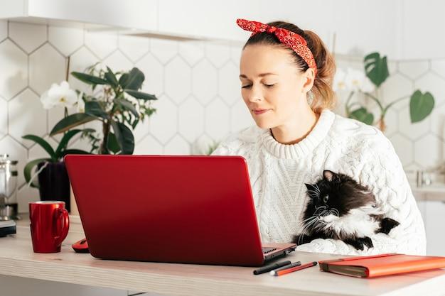 Une jeune femme est assise avec un ordinateur portable rouge à la maison dans la cuisine en bandage rouge et pull blanc et regarde le moniteur avec un chat dans ses mains. concept de travail à domicile ou d'étude