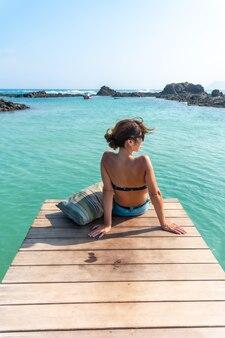 Une jeune femme est assise sur la passerelle en bois sur isla de lobos, au large de la côte nord de l'île de fuerteventura, îles canaries. espagne