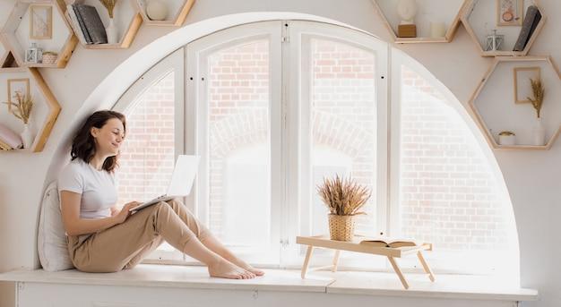 Une jeune femme est assise sur le rebord de la fenêtre dans un appartement lumineux et confortable et communique par vidéo. une femme séduisante utilise un ordinateur portable pour son travail