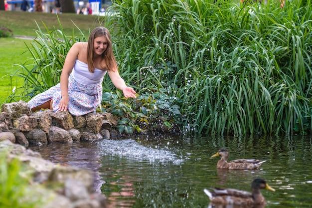 Une jeune femme est assise sur des rochers au bord de l'étang et éclabousse de l'eau sur ses canards avec sa main