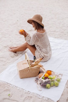 Une jeune femme est assise sur la serviette dans un chapeau de paille et un vêtement tricoté blanc avec panier de pique-nique