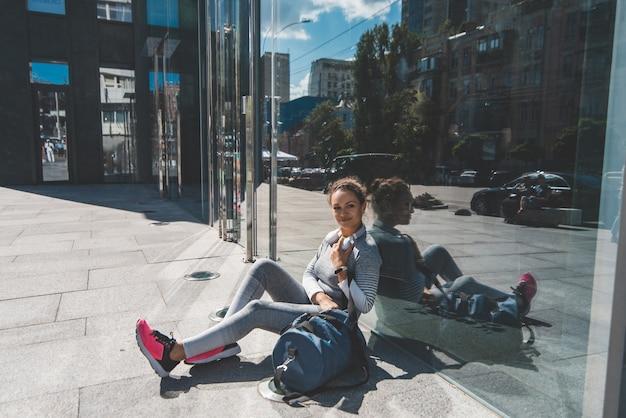 Jeune femme est assise avec ses coudes avec son dos contre un mur de verre et nous regarde