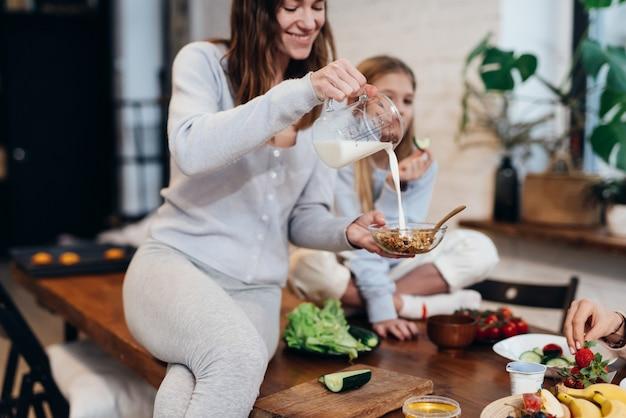 Une jeune femme est assise sur la table de la cuisine et verse du lait dans du muesli.