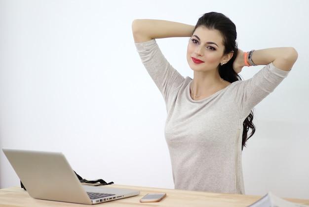 Jeune femme est assise à la table avec ordinateur portable et téléphone portable