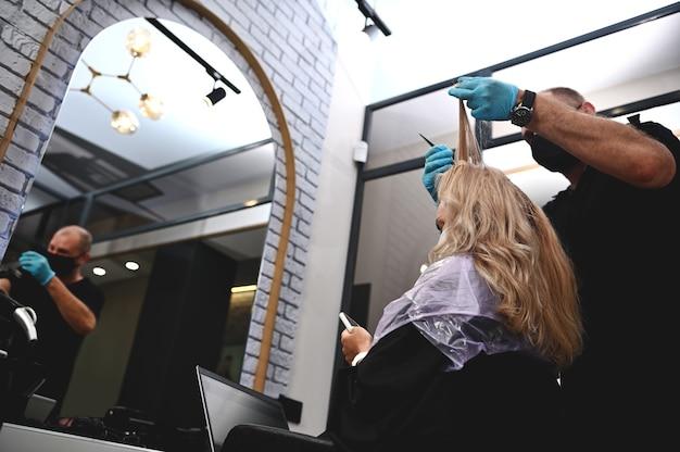 Une jeune femme est assise avec un téléphone et un ordinateur portable lors d'une teinture capillaire professionnelle dans un salon de coiffure.