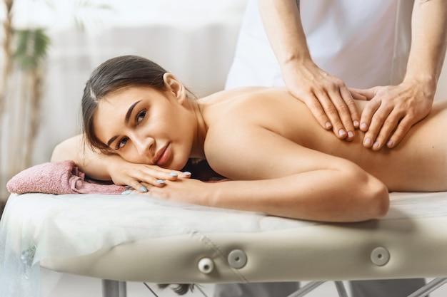 Une jeune femme est dans le salon à la réception d'un masseur se reposant pendant une séance de thérapie