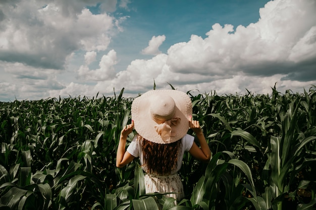 Une jeune femme est debout dans un jardin tropical regardant au loin, tenant son chapeau avec ses mains