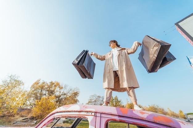 Une jeune femme est debout dans une voiture avec des sacs dans ses mains