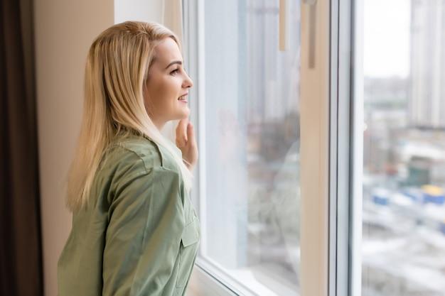 La jeune femme est debout et regarde par la fenêtre